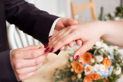Wedding rings and hands of bride and groom. young wedding couple at ceremony. matrimony. man and woman in love. two happy people c Stock Photos