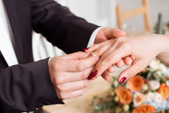 Wedding rings and hands of bride and groom. young wedding couple at ceremony. matrimony. man and woman in love. two happy people c Stock Photo