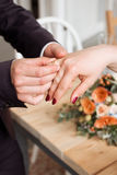 Wedding rings and hands of bride and groom. young wedding couple at ceremony. matrimony. man and woman in love. two happy people c Stock Image