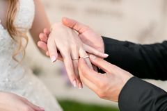 Wedding rings and hands of bride and groom. young wedding couple at ceremony. matrimony. man and woman in love. two. Happy people celebrating becoming family Stock Photo