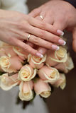 Wedding rings and Hands on wedding bouquet Stock Image