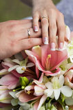 Wedding rings and hands at the wedding bouquet Stock Image