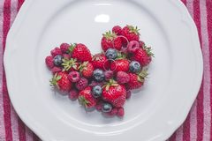 Wedding rings and heart of berries. Wedding rings on the heart of berries Stock Photo