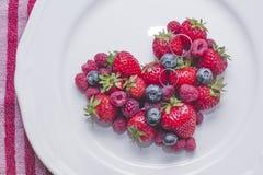 Wedding rings on heart of berries. Wedding rings on the heart of berries Stock Photography