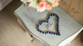 Wedding rings in a heart of a blueberry on a table, next to a br stock video