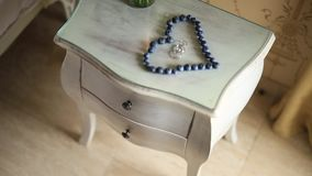 Wedding rings in a heart of a blueberry on a table, next to a br. Anch of an olive tree stock video footage