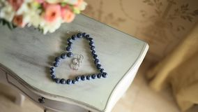 Wedding rings in a heart of a blueberry on a table, next to a br. Anch of an olive tree stock footage