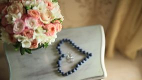 Wedding rings in a heart of a blueberry on a table, next to a br stock footage