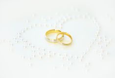 Wedding Rings with Heart of pearls. Gold Rings for a Wedding Day and Heart of pearls Royalty Free Stock Images