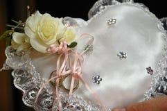 Wedding rings on heart pillow Stock Photo
