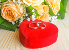 Wedding rings. On a heart shaped box  and  flowers Royalty Free Stock Image