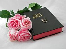 Wedding rings on holy bible Stock Photos