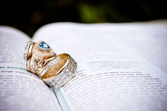 Wedding Rings. Husband and wife wedding rings.  Blue triangle diamond cut shape with gold. Rings placed on the Bible Royalty Free Stock Photos