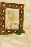 Golden Rings Golden in Golden Pearly Frame. Gold wedding bands on a creamy silk material next to a ceramic cream colored cherub  in a golden picture frame with Royalty Free Stock Image