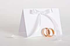 Wedding rings and invite with white bow. Two gold wedding ring and empty invite with white bow. High key Royalty Free Stock Photos