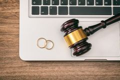 Wedding rings and judge gavel on computer laptop, wooden background, top view royalty free stock photo