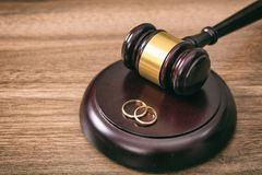 Wedding rings and judge gavel on wooden background, copy space royalty free stock photo