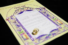 Ketubah - marriage contract in jewish religious tradition. Wedding rings and Ketubah - a prenuptial agreement in jewish religious tradition Stock Photography