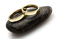 Wedding rings laying on pebble Stock Photo