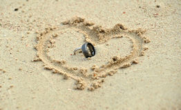 Wedding rings laying in sand in heart shape. Close up wedding rings laying in sand in heart shape symbol Stock Image