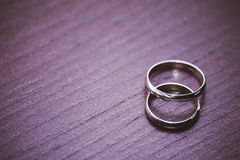 Wedding rings laying on wooden table Stock Images
