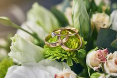 Wedding rings lie on a beautiful bouquet as bridal accessories stock images