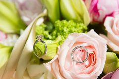 Wedding rings lie on a beautiful bouquet as bridal accessories.  Stock Photography