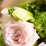 Wedding rings lie on a beautiful bouquet as bridal accessories.  Stock Photos