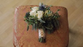 Wedding rings lie on a beautiful wedding bouquet which lays on the chair.  stock footage