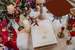 Wedding rings bible decor flowers candles table. Wedding rings lie on the bible on the table with decorations and flowers Stock Image