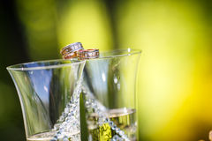 Wedding rings lie on champagne glasses Stock Photo