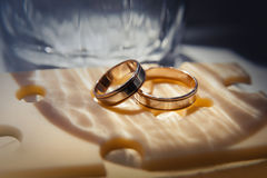 Wedding rings lie on a cheese slice Stock Photos