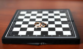 Wedding rings lie on a chessboard Stock Photo