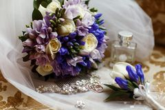 Wedding rings lie in front of the wedding bouquet stock photography