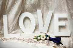Wedding rings lie in front of the word Love stock photography