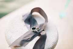 Wedding rings lie on a gray ribbon Stock Photos
