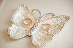 Wedding rings lie on a plateau in the form of a butterfly Stock Images