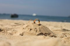 Wedding rings lie on sand castle. Wedding concept - Wedding rings lie on sand castle and mountain at Patong Beach Thailand Stock Photos