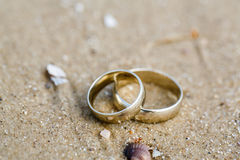 Wedding rings lie on sand. Wedding concept - wedding rings lie on sand Stock Photo
