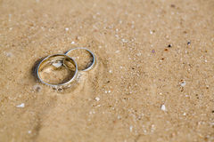 Wedding rings lie on sand. Wedding concept - wedding rings lie on sand Royalty Free Stock Photos