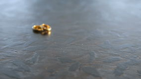 Wedding rings lie on the stone surface. Sliding camera. HD stock video footage