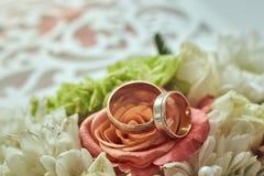 Wedding rings lie on the table near a wedding bouquet stock photos