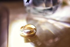 Wedding rings lie on the table near a wedding bouquet stock images