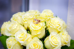 Wedding rings lie on a wedding bouquet. From roses Stock Photo