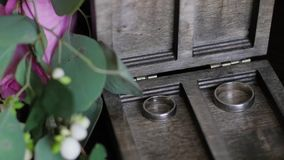 Wedding rings lie in a wooden box. Wedding bouquet on the background of rings. Slow motion stock video footage