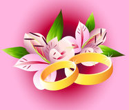 Wedding rings with lilies Stock Images