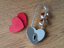 Wedding rings in the lock and two red hearts Royalty Free Stock Photo
