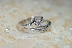 Wedding rings with love. From platinum on the bride dress Stock Photos
