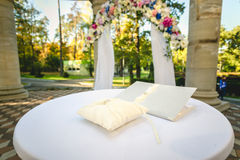 Wedding rings lying on cushion at decorated table Stock Photo
