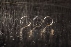 Wedding rings lying on dark surface shining with light. Water splashes. Rain stock photo